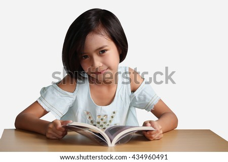 Little asian girl reading a book on the table, Isolated on white background