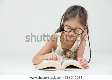 Little Asian girl reading a book with lovely Persian kitten on isolated