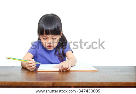 Little asian girl sitting and writing in notebook. Isolated on white background