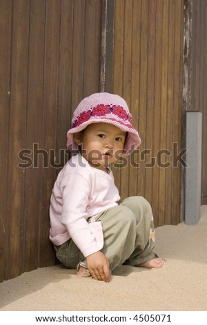 little asian girl sitting at the beach - stock photo