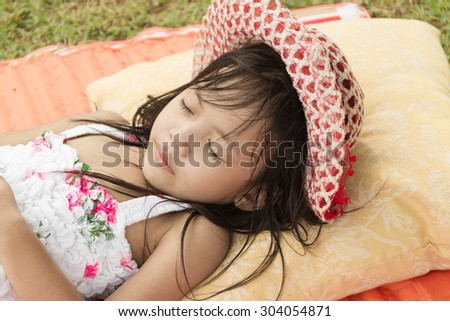Little asian girl  sleep in the park with her hat - stock photo