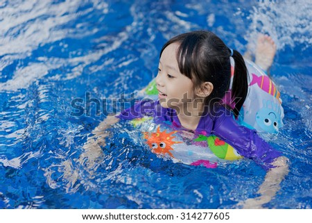 Little Asian girl swimming in a pool in a life preserver - stock photo
