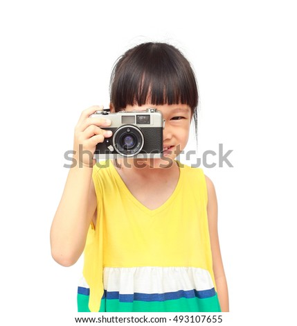Little asian girl takes picture with vintage camera
