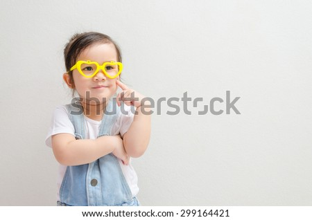 little asian girl thinking or dreaming and  smilingly - stock photo