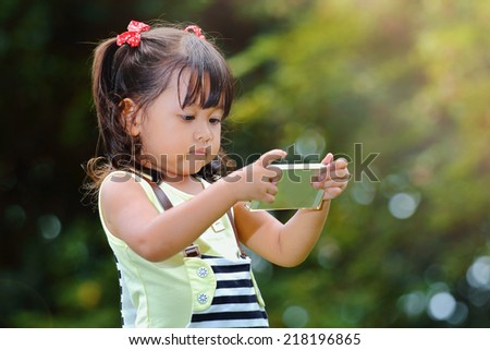 Little asian girl was playing smart phone happily in the park - stock photo