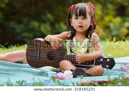 Little asian girl was playing ukulele happily in the park - stock photo