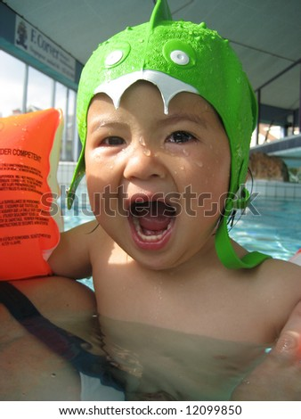 little asian girl wearing a monster swimhat - stock photo