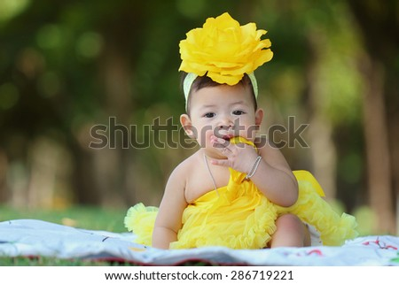 Little asian girl wearing a yellow dress was playing happily in the park, close up - stock photo