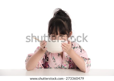 Little asian girl wearing kimono and eating noodles on white background isolated - stock photo