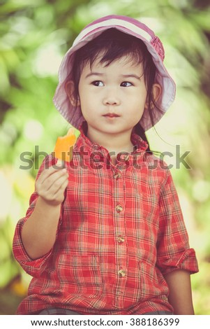 Little asian girl wearing pink hat and eating ice cream in the summer on blurred nature background. Pretty child in nature. Outdoors. Cross process.