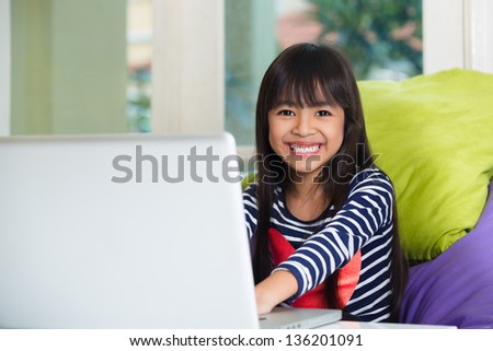 Little asian girl  with computer at home - stock photo