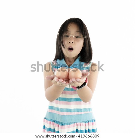 Little asian girl  with  eggs in hand on white background