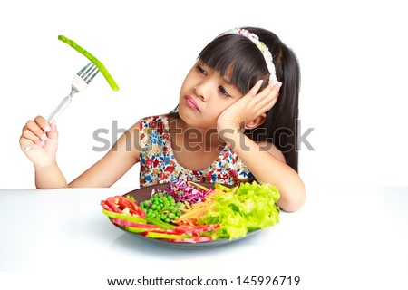 Little asian girl with expression of disgust against broccoli, Isolated over white - stock photo