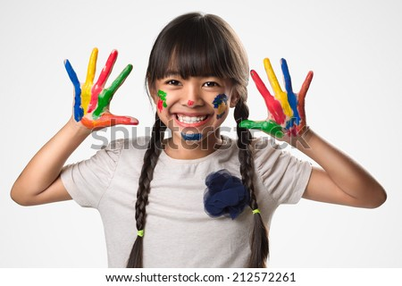 Little asian girl with her hands in the paint, Isolated over white - stock photo