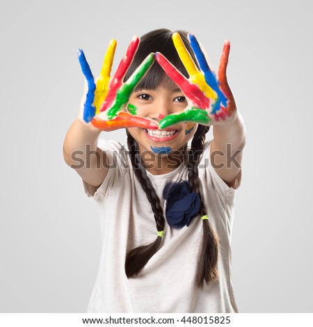 Little asian girl with her hands in the paint, Isolated over white