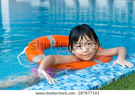 Little Asian girl with orange water ring in swimming pool