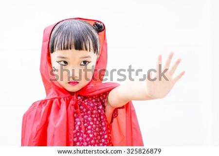 Little Asian girl with witch costume and pose; kid pose for Halloween concept; Isolated white background - stock photo