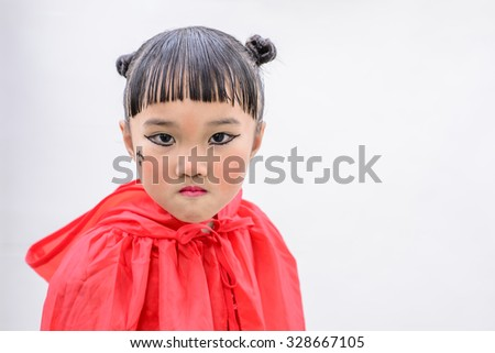 Little Asian girl with witch costume and pose; kid pose for Halloween day