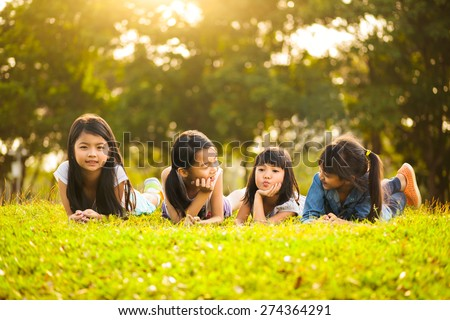 Little asian girls laying on the green grass under sunlight - stock photo