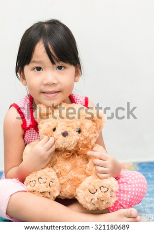 Little asian gril hug teddy bear
