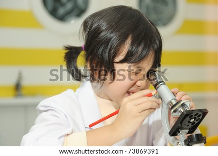 Little Asian kid looking into a microscope - stock photo