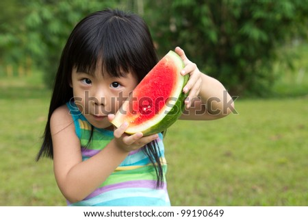 Little Asian kid with a piece of watermelon in park - stock photo