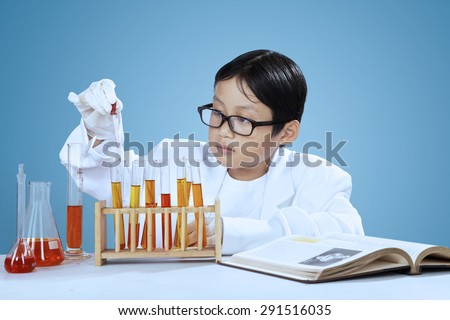Little asian scientist using pipette for dropping chemical, shot in laboratory - stock photo