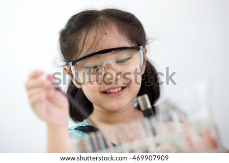 Little Asian student girl with protection glass making science experiment in the laboratory room