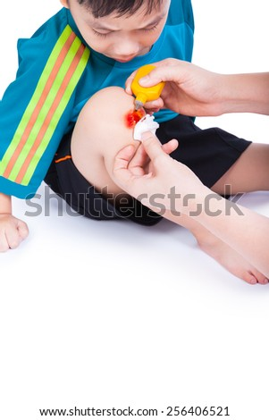 Little asian (thai) boy looking wound his leg, Nurse provides first aid, shoot in studio, Isolated on white background - stock photo