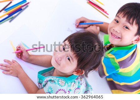 Little asian (thai) children happily, brother and sister looking at the camera and smiling. Concepts of creativity and education, strengthen the imagination of child. Studio shot. - stock photo