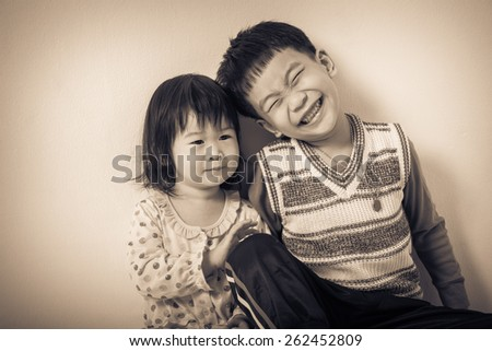 Little asian (thai) children happily, brother and sister smiling, loving and bonding of sibling concept. Cream tone background. Vintage picture style - stock photo