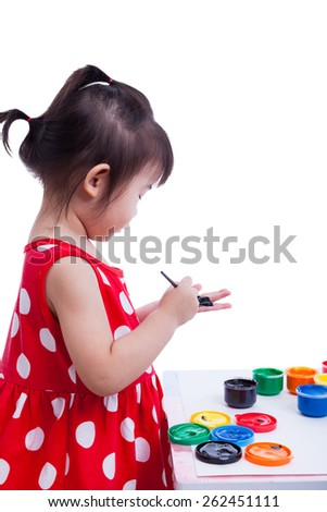 Little asian (thai) girl painting her palms using multicolored drawing instruments (watercolor paints, paintbrush), creativity concept, isolated on white background, studio shot - stock photo