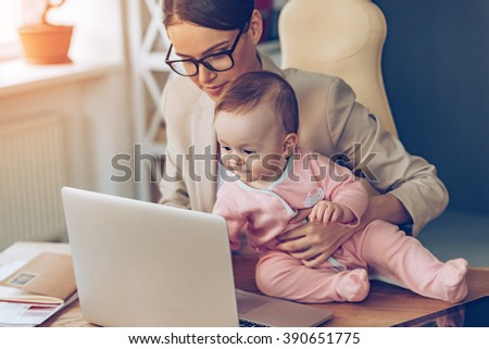 Little assistant. Little baby girl using laptop while sitting on office desk with her mother in office - stock photo