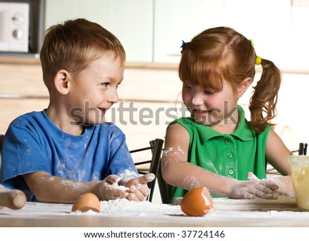 Little assistants on kitchen - stock photo