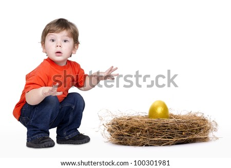 Little astonished boy with a nest and a gold egg in it. Isolated on white. - stock photo