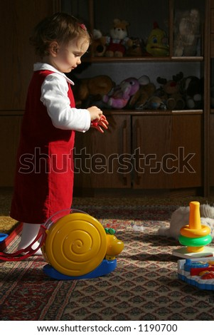 Little baby among her toys - stock photo