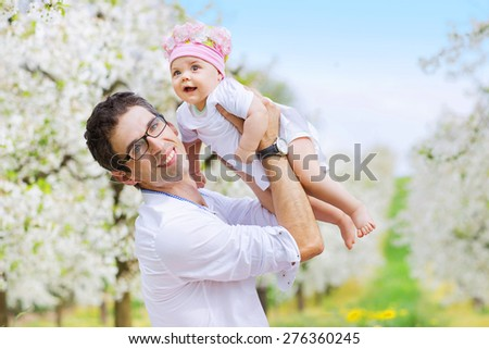 Little baby and father having fun outdoors - stock photo