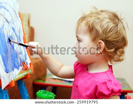 Little baby artist is painting with watercolor - stock photo