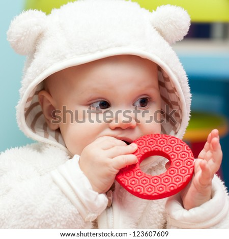 little baby baby chews on a soft plastic toy in white bear costume - stock photo