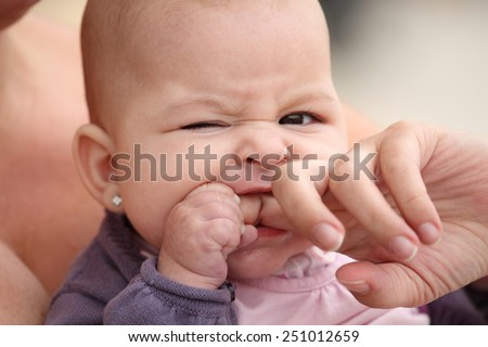 little baby biting her mother finger - stock photo