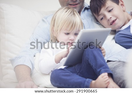 Little baby boy and family playing with tablet