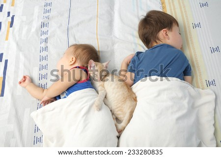 Little baby, boy and kitten sleeping together - stock photo