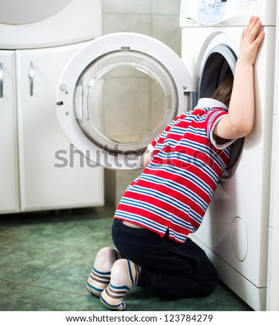Little baby boy dangerously putting his head into washing machine - danger in bathroom - stock photo