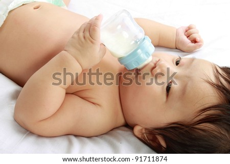 little baby boy drinks milk from bottle holded by him self, lying on bed - stock photo
