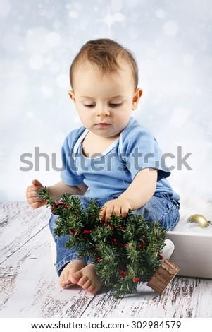 Little baby boy exploring christmas tree - stock photo