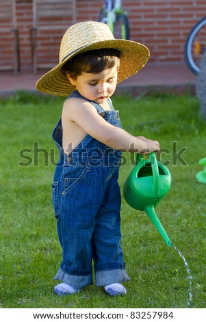 little baby boy gardener playing in his front yard - stock photo