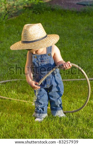 little baby boy gardener playing to fix the hose - stock photo