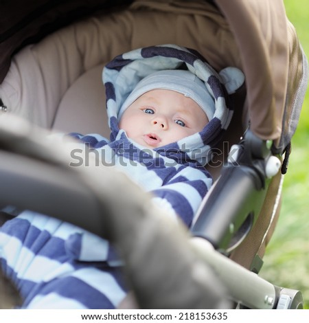 Little baby boy in stroller outdoors - stock photo