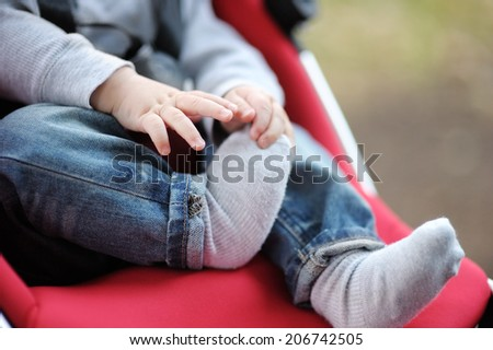 Little baby boy in stroller playing with his sock  - stock photo