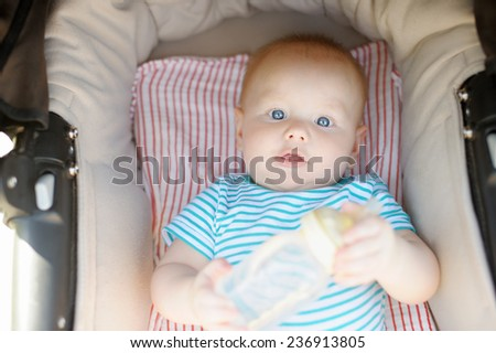Little baby boy in stroller with bottle of water at summer day